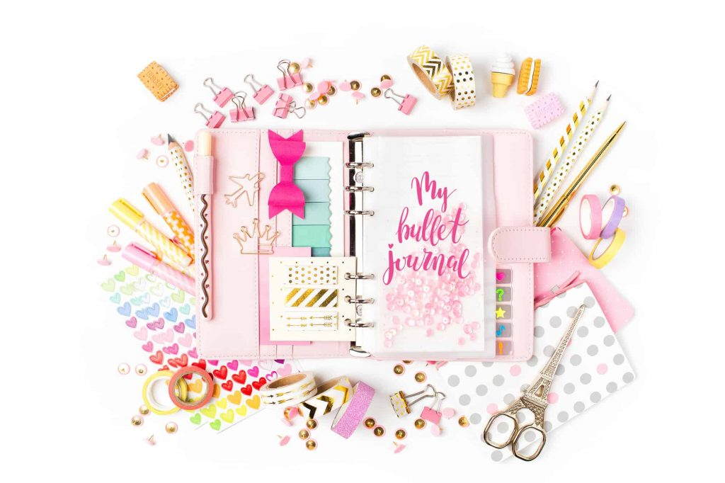 image of journal with accessories surrounding and text for what is a bullet journal