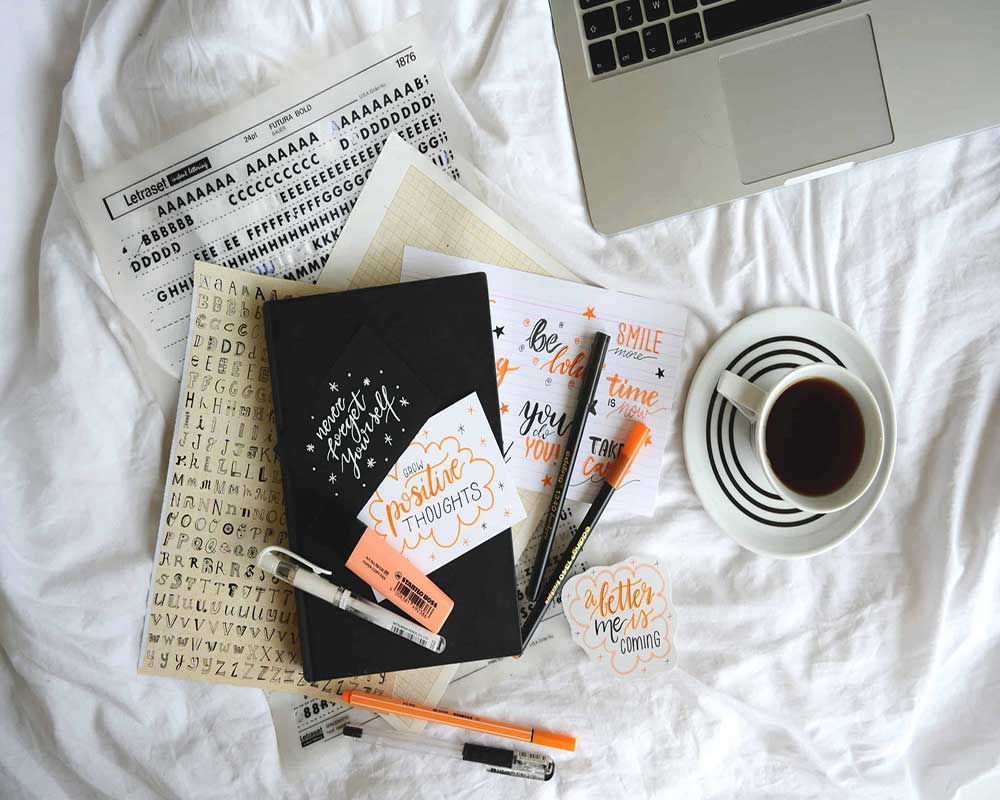 image of bullet journal and supplies coffee cup and laptop on bed as example for What Is A Bullet Journal