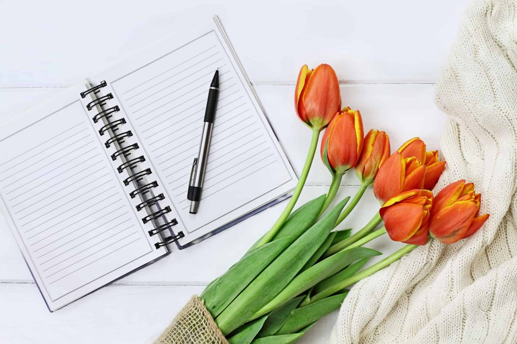image of surface with open notebook pen flowers for how to start a self care journal
